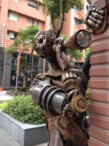 A robotic sculpture peeks around a corner.